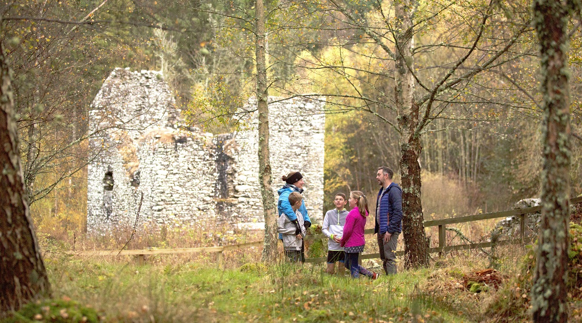 A family standing in front of the ruins of Cardrona Tower