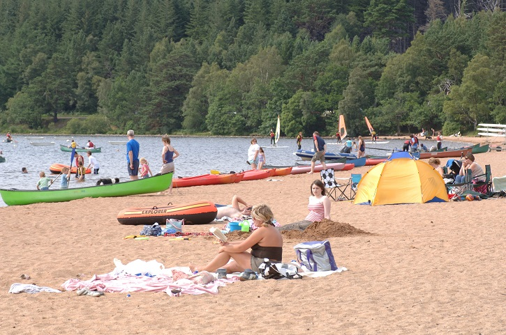 People sunbathing and playing on a beach next to a loch with forest beyond