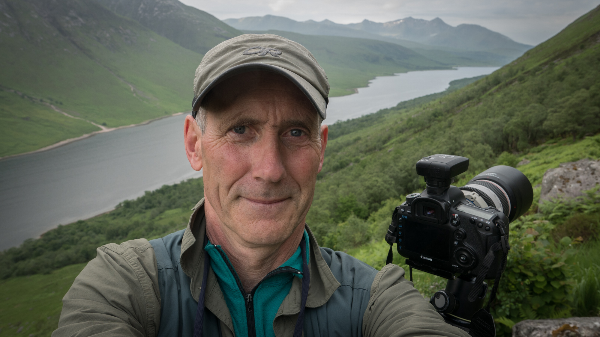 Older man taking a selfie photo with steep sided green slopes behind leading to a long, thin body of water