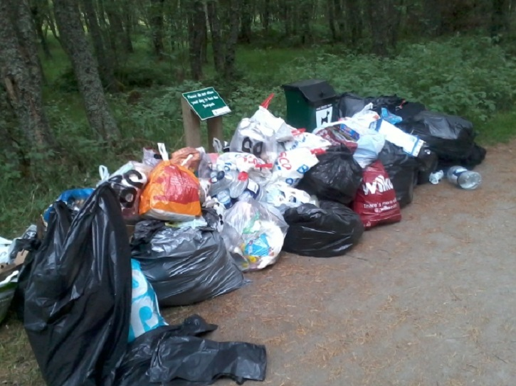 Numerous bags of litter and rubbish piled up on a gravel track besides some trees
