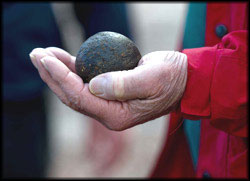 A person holding a palm sized canon ball, made of iron.