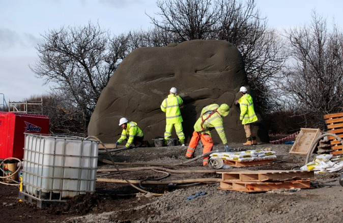 Workers in hi-vis jackets sculpting large boulder with trees beyond