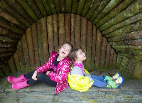 Two young girls sitting back-to-back in a wooden den
