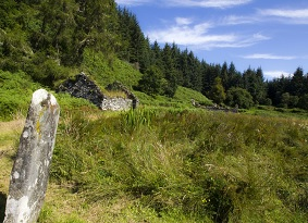 A standing stone and ruins of a stone building