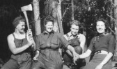 A group of lumberjills pose together, one is holding up an axe.