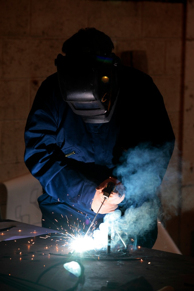 Man in workshop wearing large industrial facemask welding