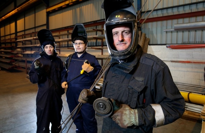 Three men in dark overalls and face masks looking at camera in large workshop