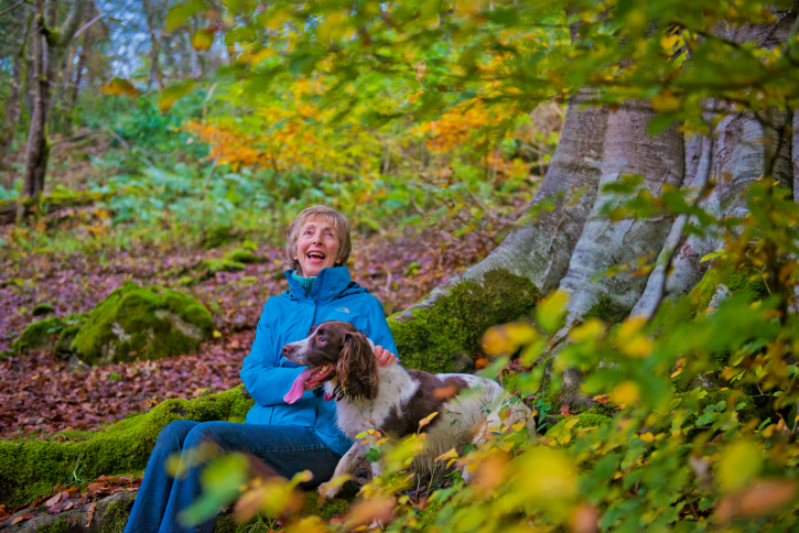 Lady with her dog in autumn forest