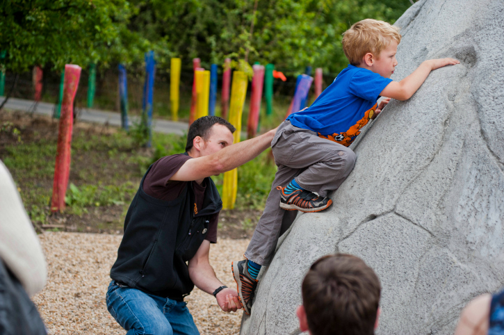 man helping a boy up an outdoor boulder