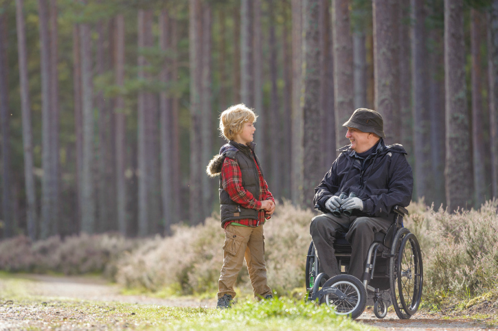 boy and man in wheelchair talk beside tall trees