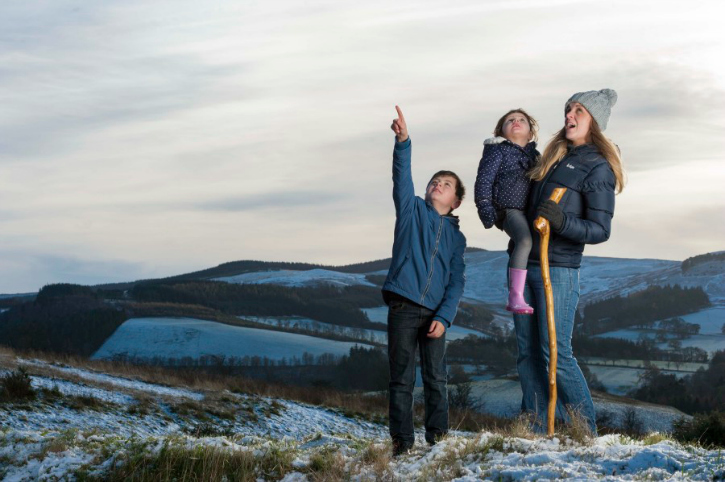 mother and two sons stand on snowy hill
