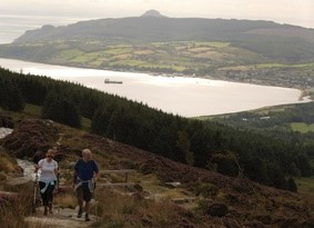 Two people walking up a hill path overlooking a large bay