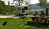 A couple and a dog at a picnic bench, their campervan parked behind them