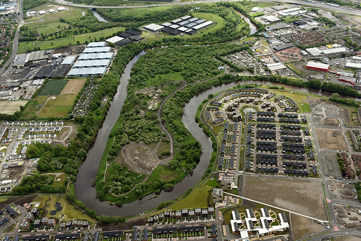 Aerial photograph of mixed use land containing trees, waterway and industrial sites