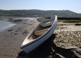 Small rowing boat on shore in front of a forested hill