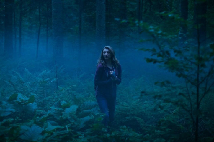 woman walking through spooky forest in the dark