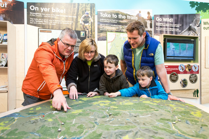 family looking at model of area on a large table in info centre