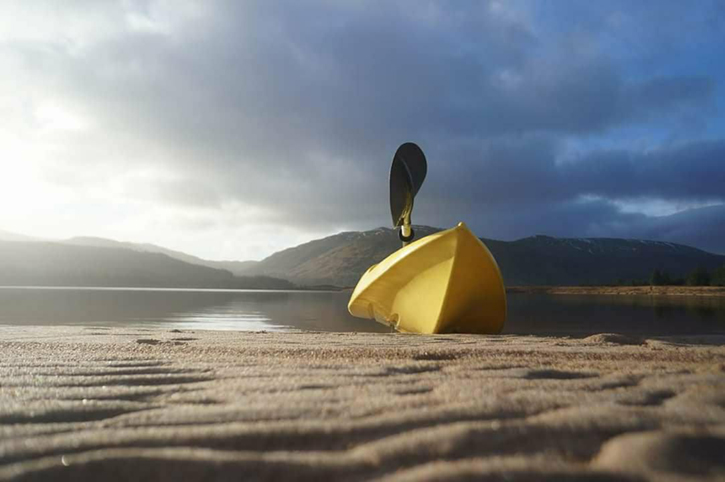 A yellow kayak pulled up onto a beach with loch, hills and grey sky behind