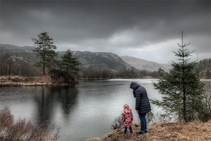 Adult and child standing beside loch under a threatening grey cloud